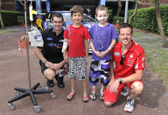 Shane van Gisbergen and James Courtney with two children at Westmead Children's Hospital
